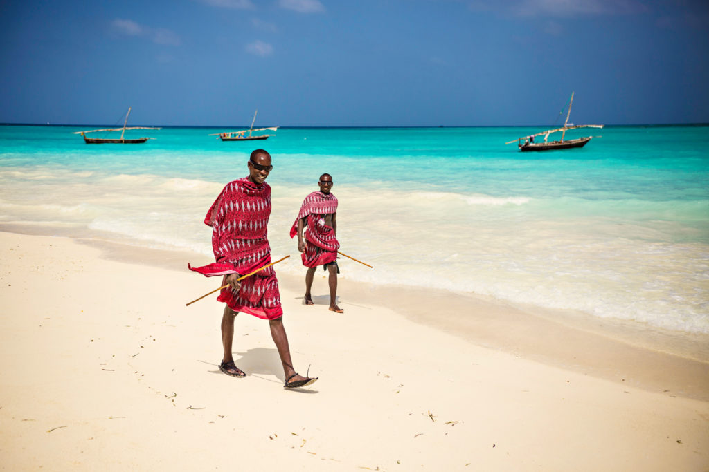 Two Masai walk along a beach in Zanzibar